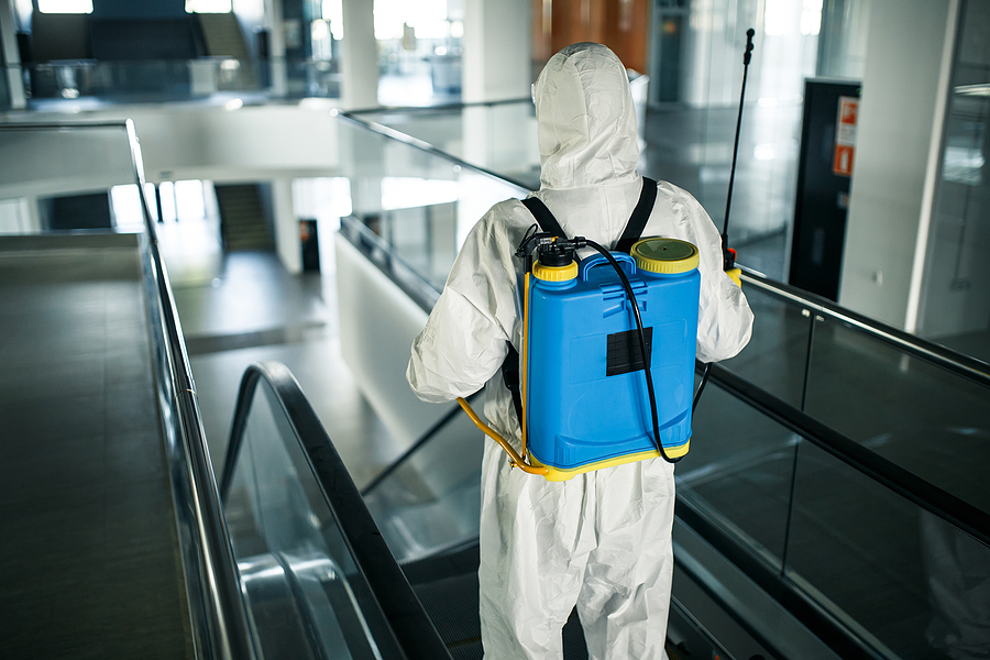 disinfection worker wearing a protective suit professionally cleans up an escalator in an empty business center.